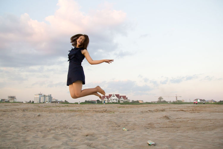 Woman jumping at beach against sky