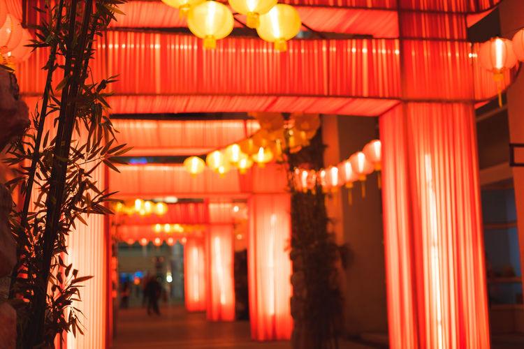 Illuminated lanterns hanging in building at night