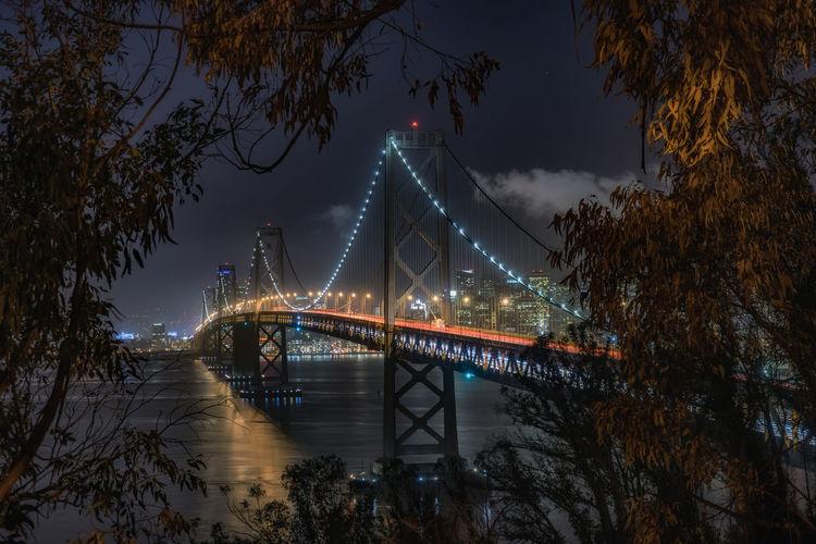Illuminated bay bridge over river against sky at night