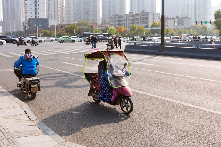 People riding bicycle on road in city