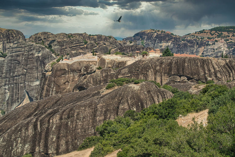 Scenic view of rocks against cloudy sky