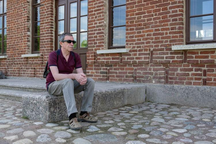 Full length of man sitting on brick wall