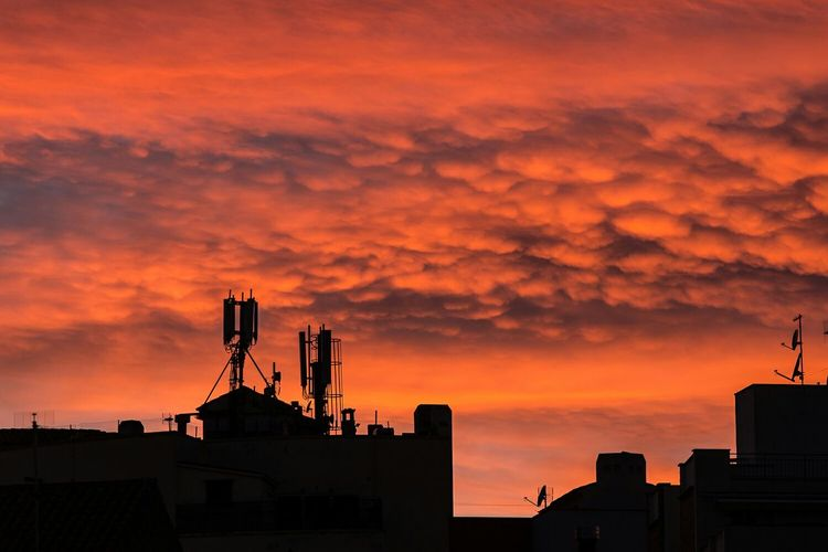 Silhouette Buildings Against Cloudy Sky At Sunset