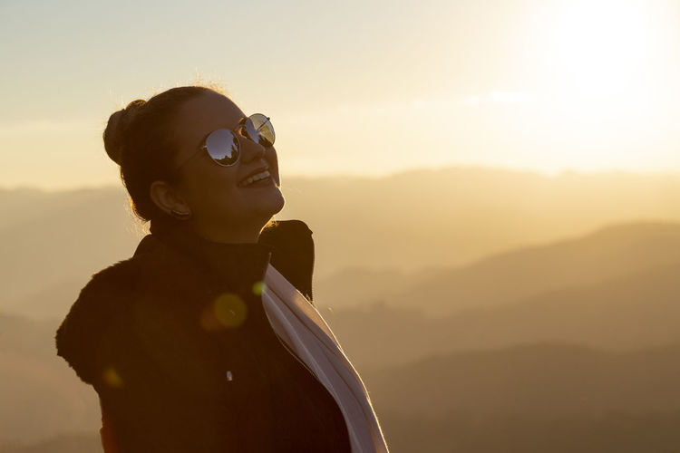Woman wearing sunglasses and warm clothing during sunset
