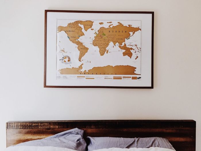 Bed against world map on wall at home