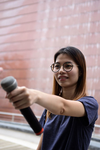 Female journalist with microphone standing against building