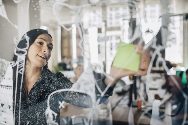 Businesswoman sticking adhesive note on patterned glass in creative office