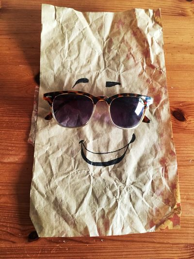 High angle view of anthropomorphic face made with crumpled paper and sunglasses on wooden table