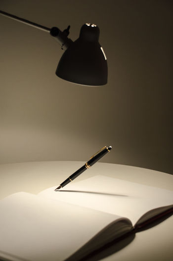 Fountain pen on open book with illuminated lamp in room