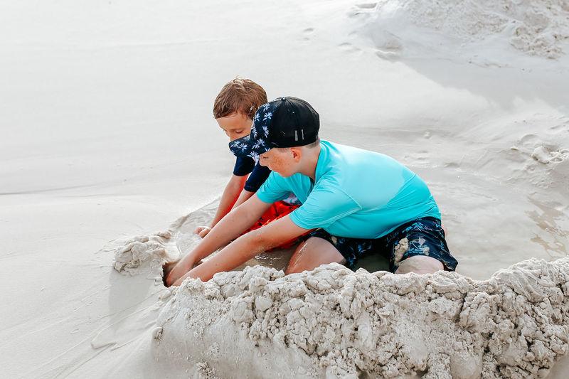Rear view of boys on beach