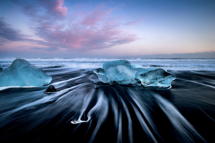 Long exposure of waves in sea against sky during sunset