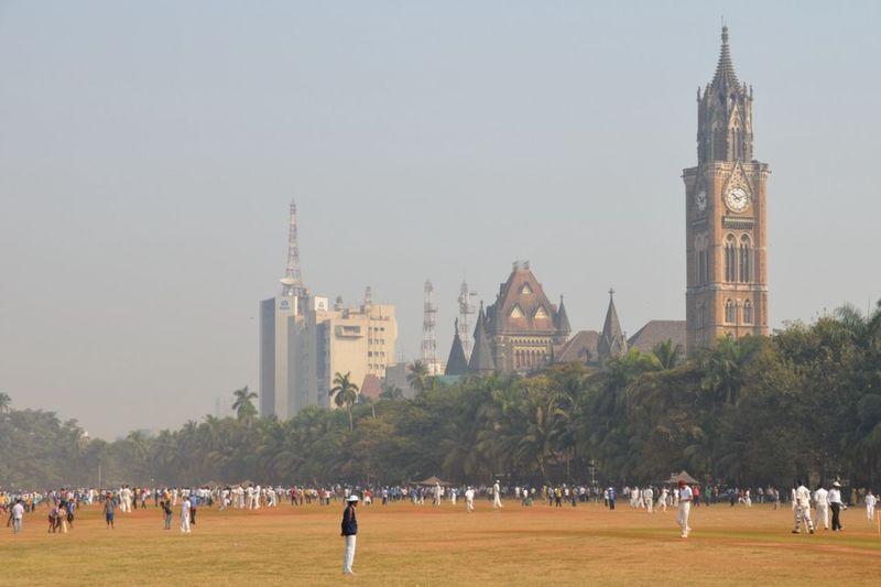 Playing cricket at Oval Maidan with clock tower behind at Mumbai, Maharashtra, India
