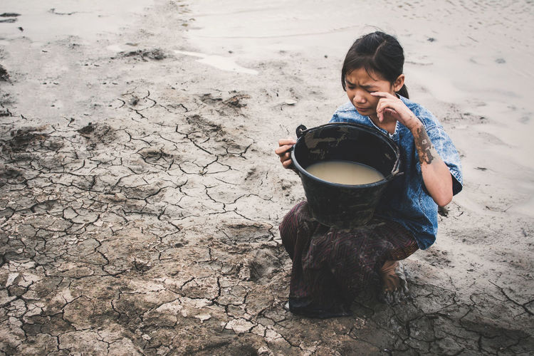 Girl with water in bucket sitting at beach