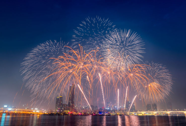 Low angle view of firework display over river against sky