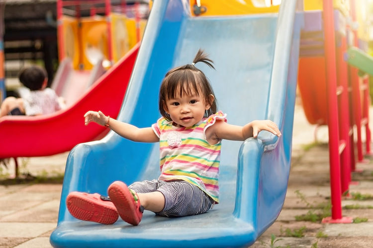 Portrait of girl on slide in playground