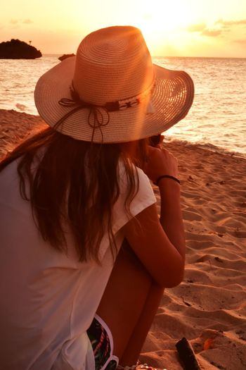 Rear view of woman wearing hat at beach during sunset
