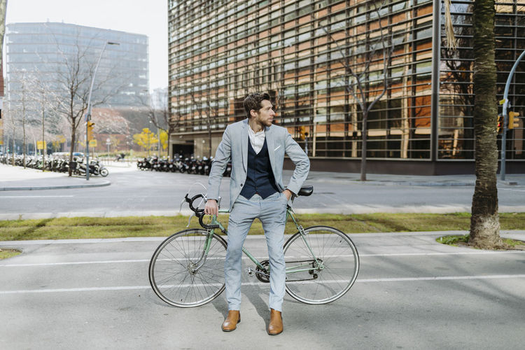 Man with bicycle on street in city