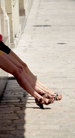 two woman leaning on a wall with long legs Beautiful Beauty Beine Carefree Enjoying The Sun Frauen Legs Legs_only Light And Shadow Long Legs Sandals Sommer Standing Street Street Photography Summer Summerfeeling Women