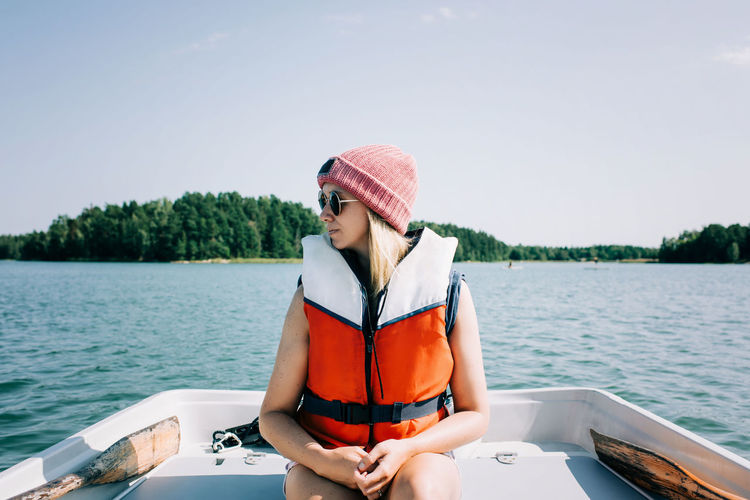 Young woman sitting on boat against sky