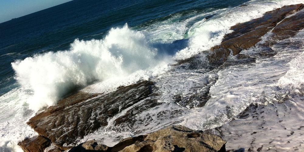 View of waves splashing on rocky shore
