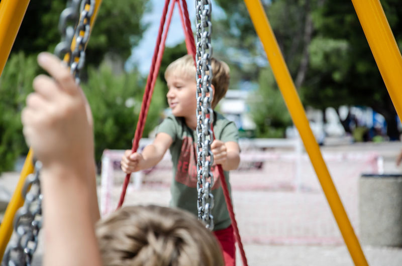 Children playing on swing at playground