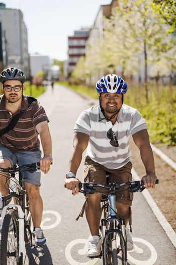 Portrait of people riding bicycle on city