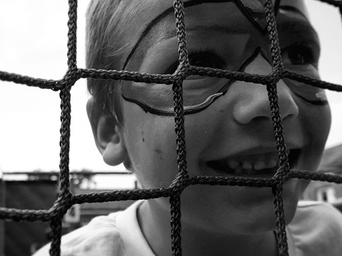 Close-up of smiling boy with face paint seen through net