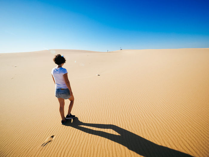 Rear view of woman standing on sand dune
