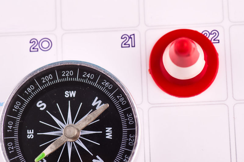 close-up image of compas on planner calendar Close-up Number Guidance Indoors  No People Still Life Communication Accuracy Text Navigational Compass Geometric Shape Direction Shape Circle Western Script Sign Arrow Symbol Technology Red Full Frame