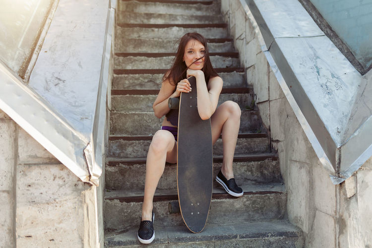 Portrait Of Smiling Young Woman With Skateboard Sitting By Steps
