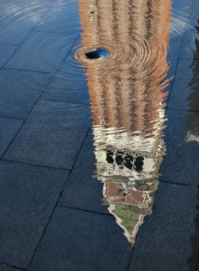 Reflection Of Tower On Puddle In Piazza San Marco