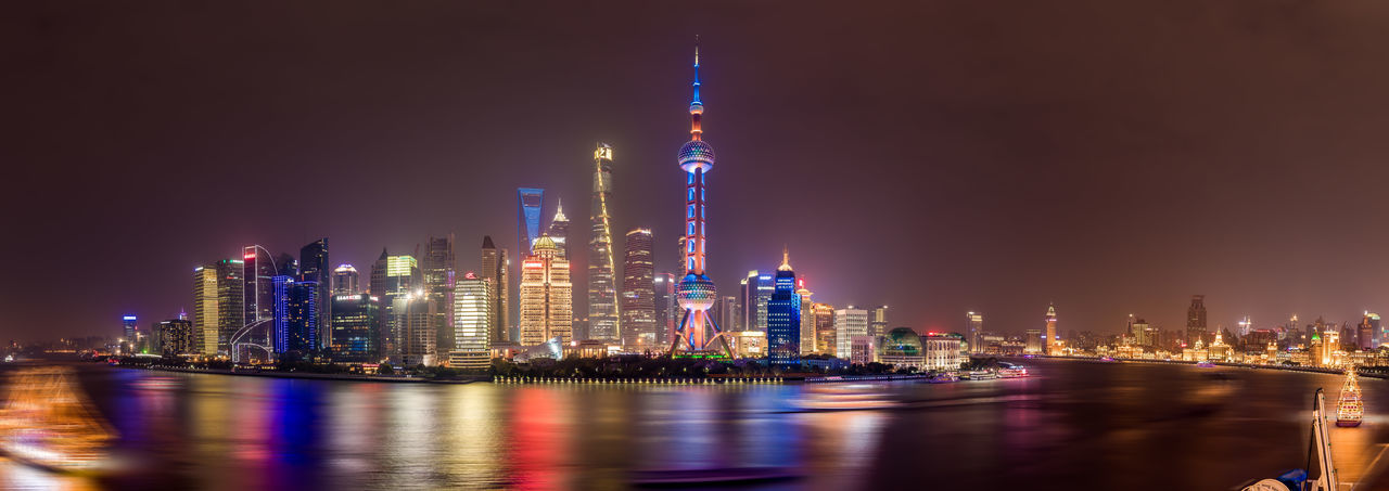 Oriental Pearl Tower By River Against Sky In City At Night