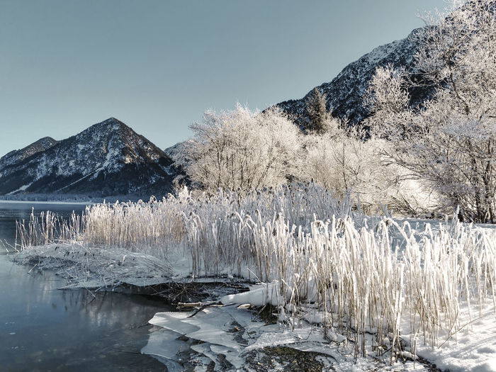 Frozen lake by mountain against sky