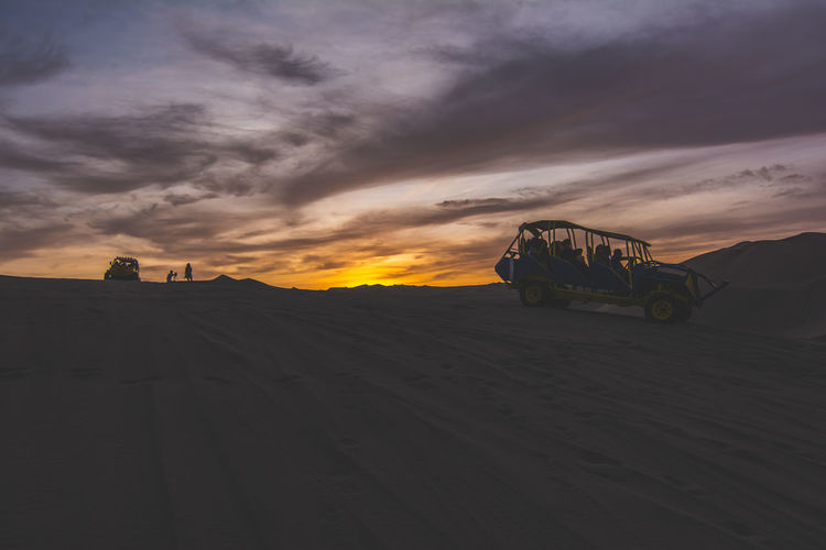 Tourists In Dune Buggy On Sand At Dusk
