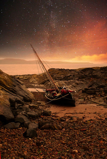 Sailboats moored on beach against sky at night