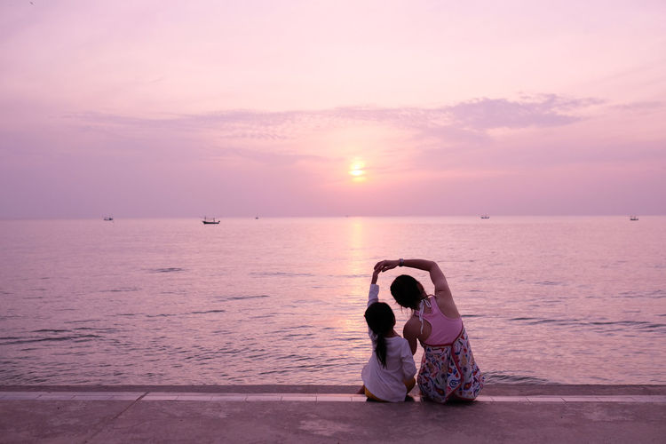 Rear view of mother with daughter sitting on footpath by sea against sky during sunset