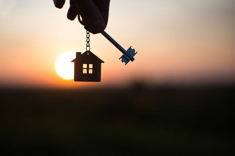 Silhouette of a house figure with a key, a pen with a keychain on the background of the sunset.