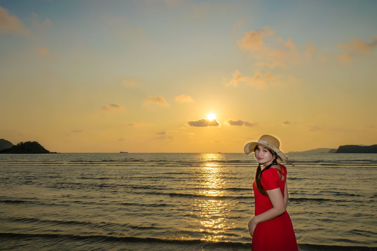 Portrait Of Young Woman Standing At Beach Against Sky During Sunset
