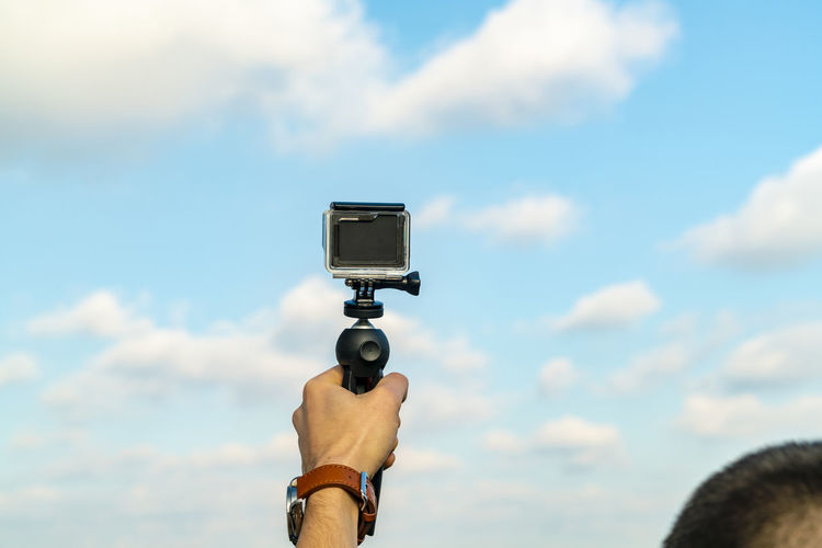 Man photographing camera against sky