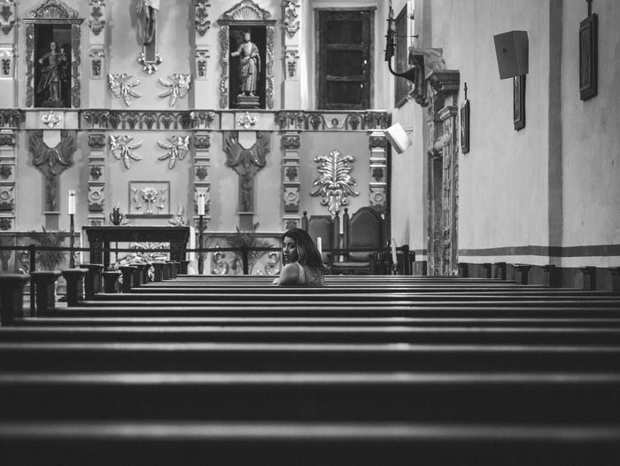 Woman Sitting On Pew At Church