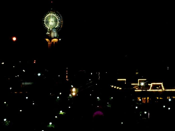 Low angle view of illuminated amusement park at night