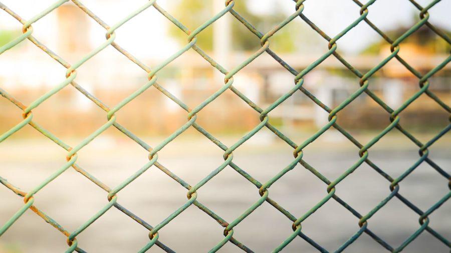 Full frame shot of chainlink fence against field