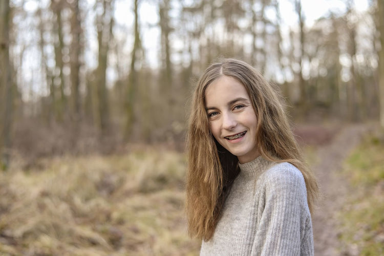 Portrait of smiling teenage girl in forest