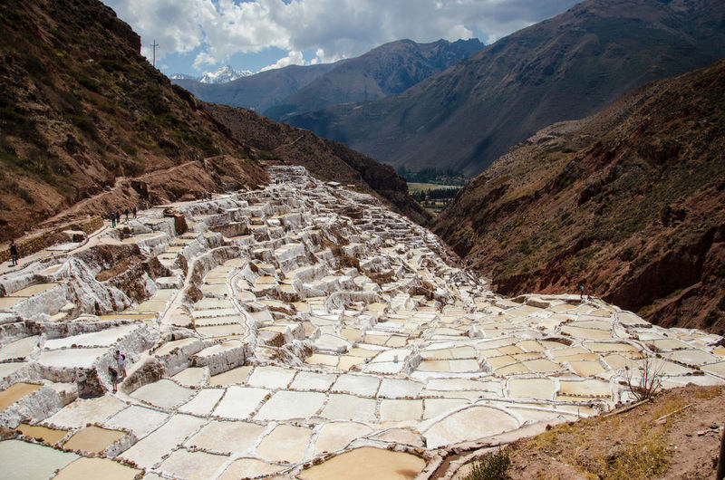 High angle view of salt pans against rocky mountains