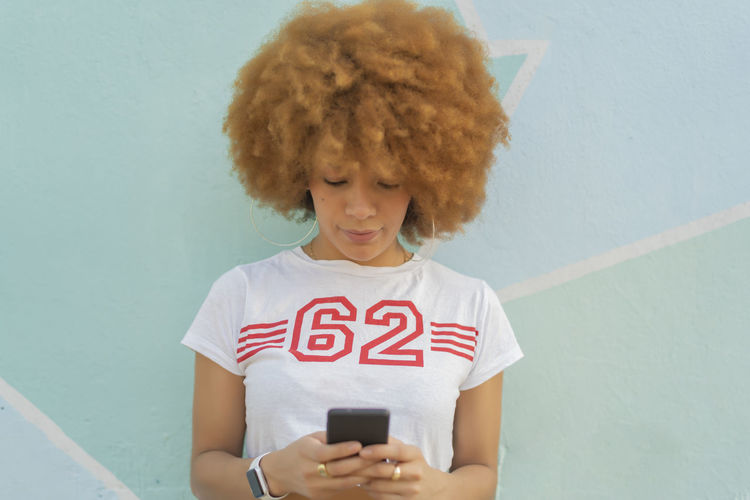Portrait of woman holding mobile phone against wall