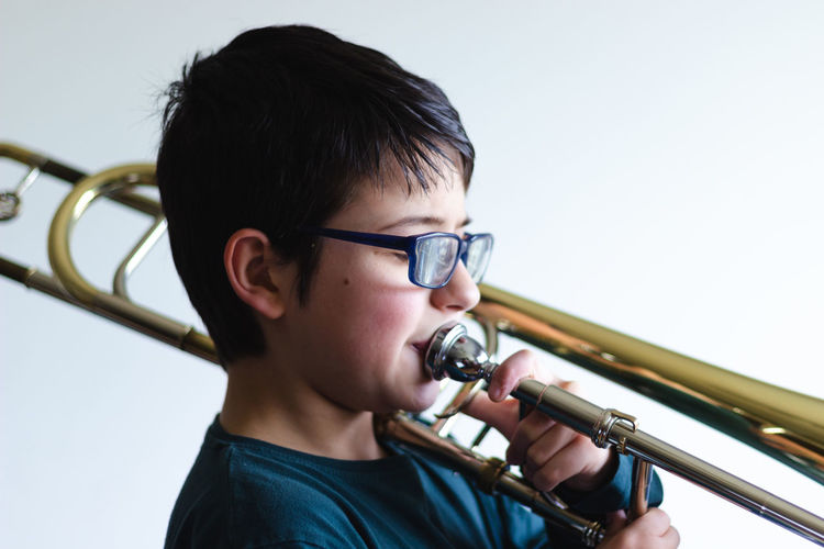 Side View Of Boy Playing Trumpet Against White Background