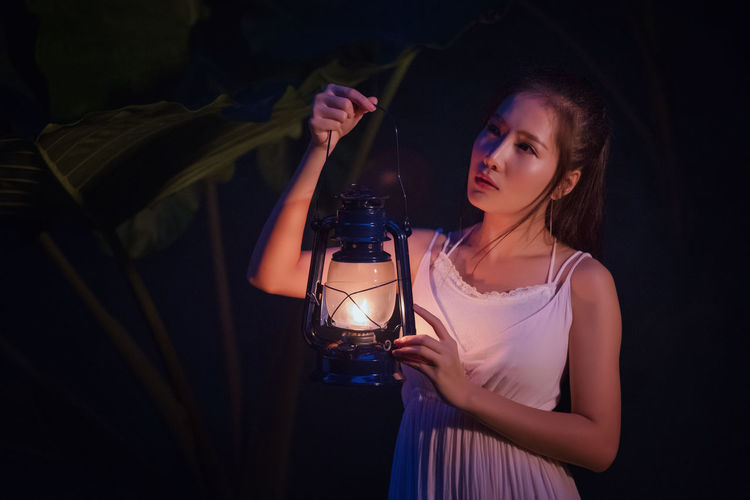Woman Holding Illuminated Lantern While Standing Outdoors At Night