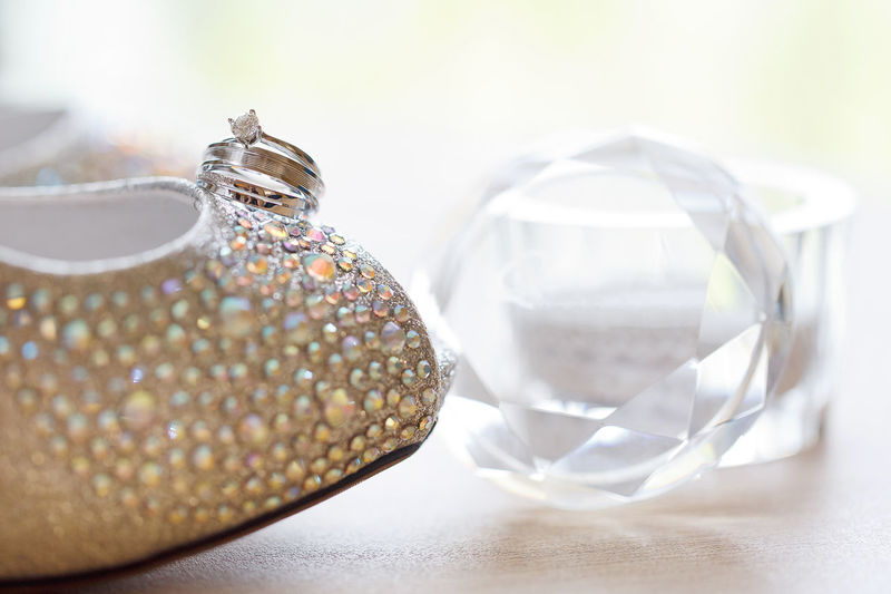 Close up elegant wedding diamond rings on glitter and twinkle women high heels shoes. Indoors  Table Still Life Close-up Jewelry No People Wealth Transparent Focus On Foreground Glass - Material Luxury Shiny Diamond - Gemstone Fashion Selective Focus Personal Accessory Pattern Elégance Silver Colored Ornate Expense Crystal Ball Box Wedding Rings