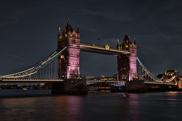 Illuminated tower bridge over thames river against sky at night