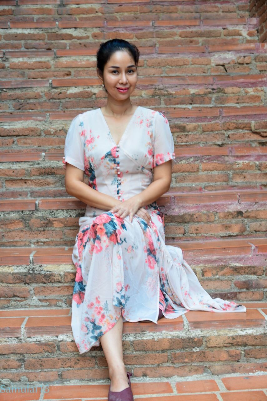 one person, front view, looking at camera, young adult, wall, women, portrait, brick wall, casual clothing, full length, lifestyles, young women, real people, leisure activity, brick, smiling, adult, wall - building feature, clothing, fashion, beautiful woman, floral pattern, hairstyle